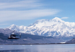 Photo of a Bell helicopter flying over icy waters with snowy mountain in the background.