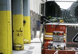 Front left side of a FDNY truck parked with yellow painted beams on the left of the image.