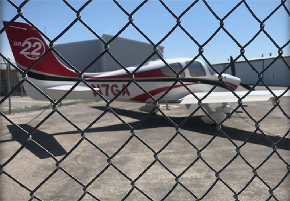 Photo of a red and white Cirrus SR 22 behind a chainlink fence
