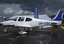 Photo of a white and blue Cirrus SR22 on a runway with grey clouds in the sky in the background.