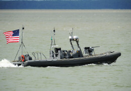 Image of a Navy rigid hull inflatable boat advancing in the water with an American flag at the bag.