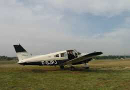 Photo of a Piper airplane on a grass landing strip.