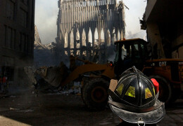 Photo of a FDNY first responder looking at a portion of one of the collapsed WTC towers.