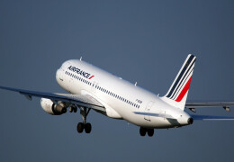 Photo of a white red and blue Air France Airbus taking off with a clear blue sky in the background.