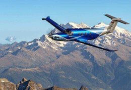 Photo of blue Pilatus PC-12 flying with mountains in the background.