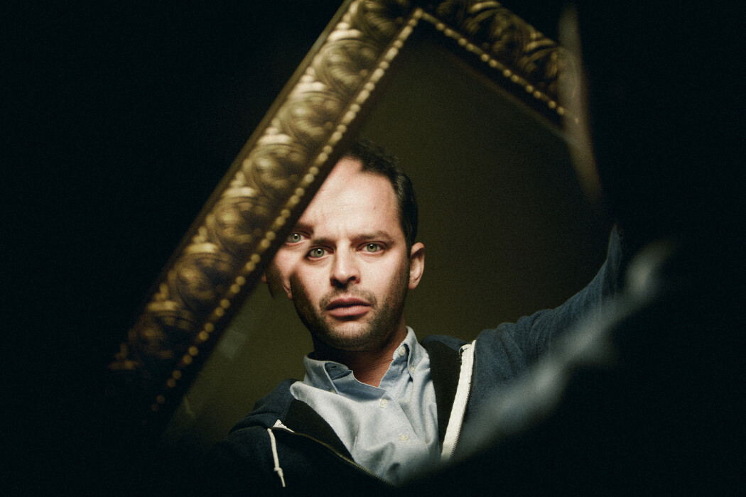 Photo of Nick Kroll in a dark rook looking at a reflection of himself  in a mirror with a gold frame.