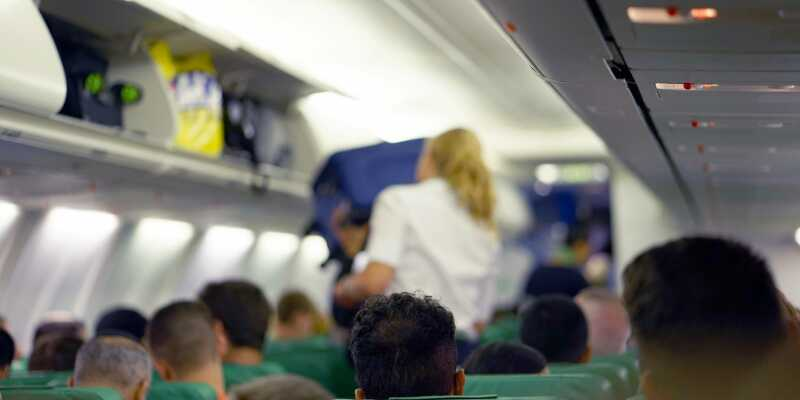 Photo or flight attendant loading luggage into overhead bin on flight.